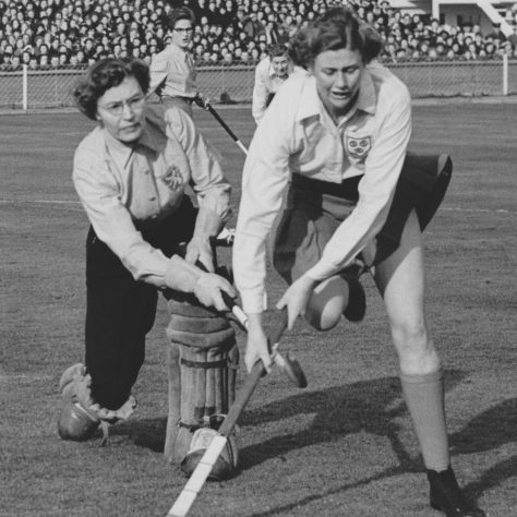 Black and white photo of England and Holland hockey players attempting to gain control of the hockey ball | Courtesy of The Hockey Museum