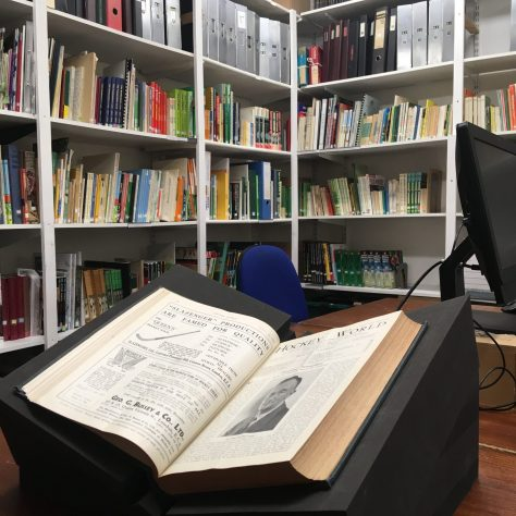 Book of hockey history propped open on a desk in front of bookshelves | Courtesy of The Hockey Museum