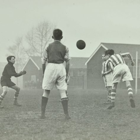 Black and white photo of boys playing football | Image courtesy of London Metropolitan Archives