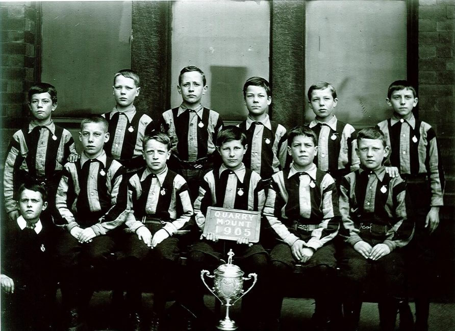 Black and white team photo of Leeds Quarry Mount School Football Team with a trophy
