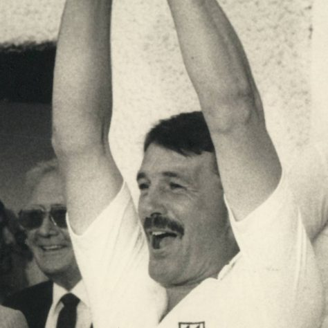 Black and white photo of Phil Neale lifting a trophy above his head