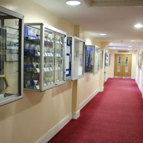 Hallway lined with various display cases | National Badminton Museum