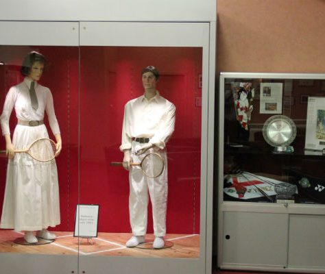 Mannequins wearing traditional Badminton attire next to a display cabinet with various memorabilia | National Badminton Museum