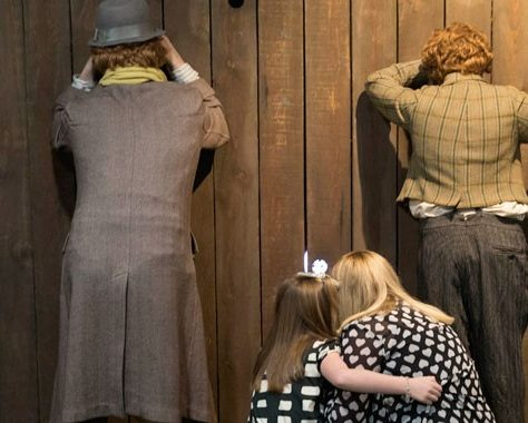 Mannequins and Museum guests peek through a fence | Scottish Football Museum