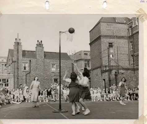 Black and white photo showing girls shooting at net in Intercounty match, Kent v Surrey, 1959 |  England Netball Heritage Archive