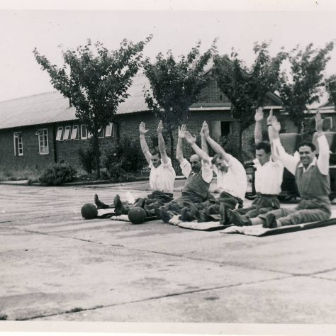 Black and white photo of five men sat in a row in on mats front of wheelchairs with arms stretched above their heads   Image courtesy of the National Paralympic Heritage Trust