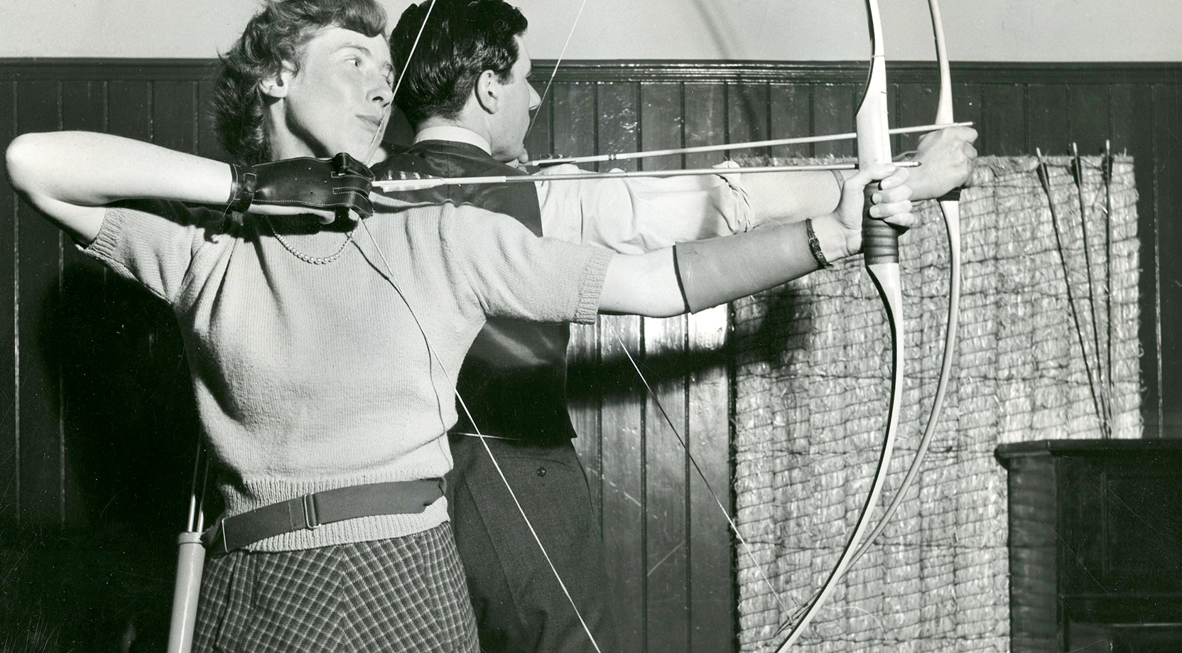 Black and white image of a male and female archer, holding a bow and arrow.