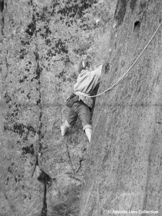 Gwen Moffat climbing a sheer rock face, with a rope as harness. | © Johnnie Lees Collection, supplied by the Mountain Heritage Trust
