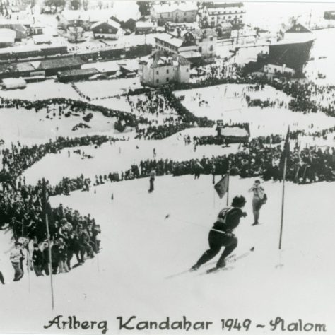 A black and white photo of a skiier doing the Arlberg Kandahar 1949 Slalom with lots of spectators along the slope | DMU Special Collections