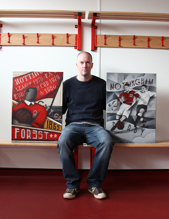 Paine Proffitt sat in a changing room holding two pieces of artwork | Paine Proffitt