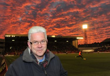 Ian McMillan stood in front of a stand at Barnsley FC Oakwell stadium at dusk | Courtesy of www.turningimages.co.uk