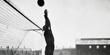 Black and white photo of goal keeper knocks ball over the top of the post