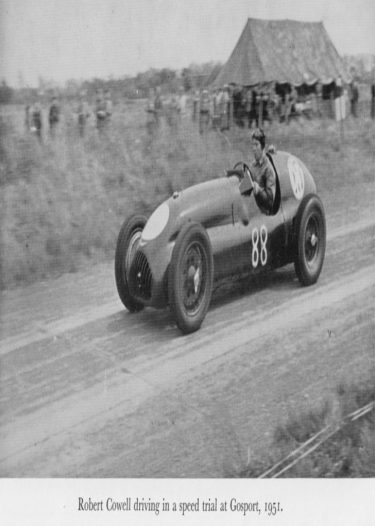 Black and white photo of racing car watched by spectators with caption
