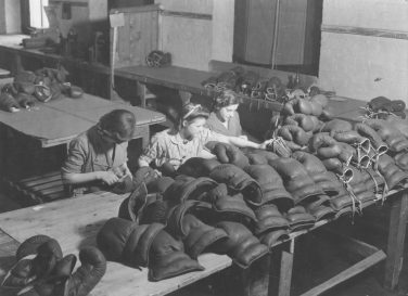 Black and white photo of Horbury workers lacing boxing gloves during the Second World War | Wakefield Museums