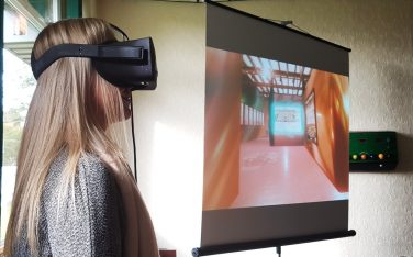 A woman wearing a virtual reality headset | One to One Development Trust