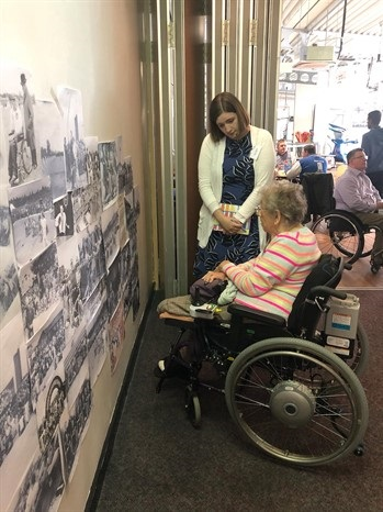 Two women in from of a wall displaying historic sporting images | National Paralympic Heritage Trust