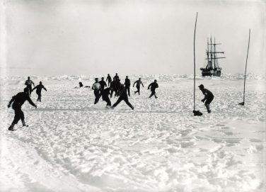 Black and white photo of people playing football in deep snow with a ship in the background   Army Museums