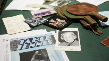 Table Tennis artefacts on a table including a badge, black and white photo and paddles | Cardiff City Table Tennis Club