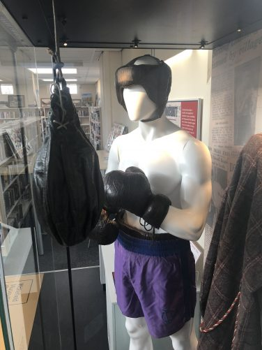A mannequin displaying historic boxing gear and an old suspended punch bag | Wakefield Libraries