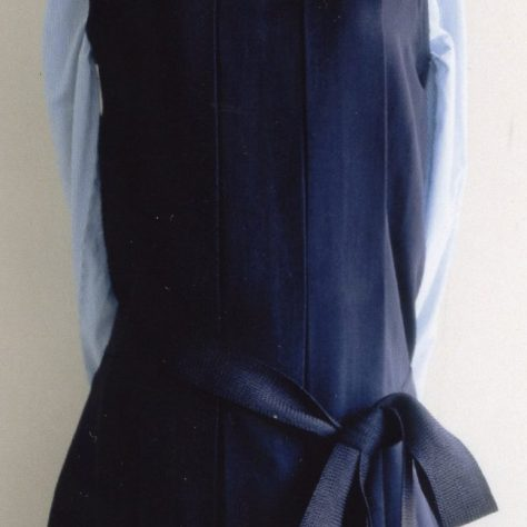 Dark blue dress with a silver brooch over a light blue long sleeve shirt displayed on a mannequin | Bergman Osterberg Union