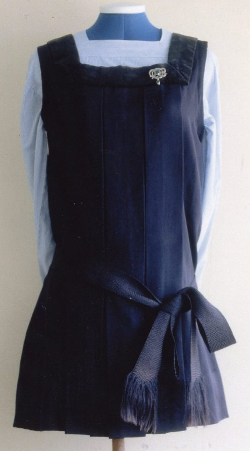 Dark blue dress with a silver brooch over a light blue long sleeve shirt displayed on a mannequin   Bergman Osterberg Union