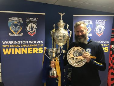 Adam Hills holding and standing in front of trophies won by Warrington Wolves | Warrington Wolves Foundation