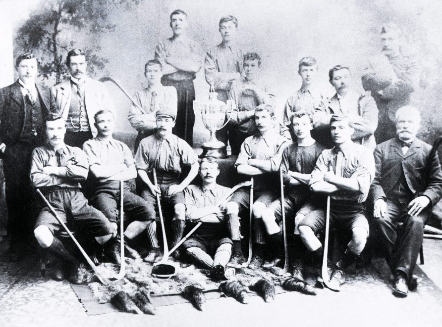 Black and white photo of a shinty team with a trophy in the centre | Highland Folk Museum