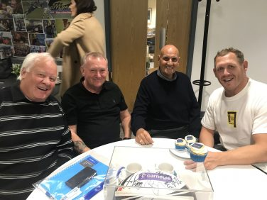 Four men sat around a table smiling at the camera with cupcakes featuring the Sporting Heritage logo | Warrington Wolves Foundation