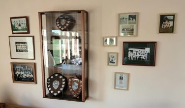 Wall mounted display of cricket trophies and images | Courtesy of Eye & District Cricket Club