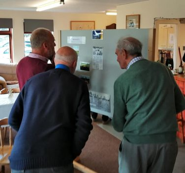 3 men observing a notice board featuring historic cricketing images and newspaper cuttings | Courtesy of Eye & District Cricket Club