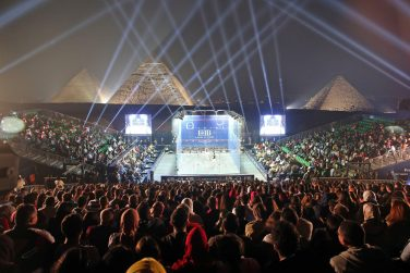 Squash court in the middle of three packed stands in front of the pyramids of Giza | Courtesy of the World Squash Library