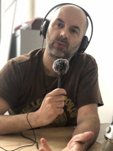 Image of Russell Todd speaking into a microphone | Russell Todd