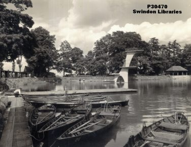 Black and white photo of boats moored on a jetty on a lake with a diving column in the background | Courtesy of Local Studies, Swindon Libraries