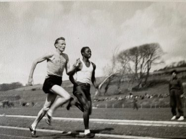 Black and white photo of two runners side by side on a track | Ann Robertson, née Davies