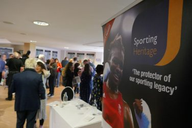 People gathered in a hall at the Sporting Heritage Summit 2019 with a poster in the foreground featuring boxer Nicola Adams | Sporting Heritage CIC