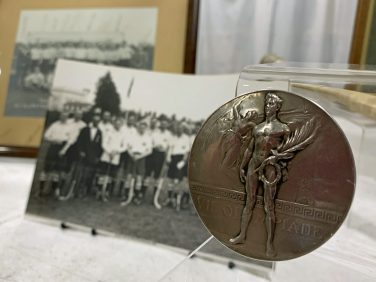 Engraved medallion in front of black and white hockey photos | The Hockey Museum