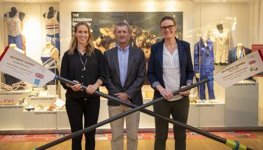 Three people pose with oars in front of an Olympic rowing display | River and Rowing Museum