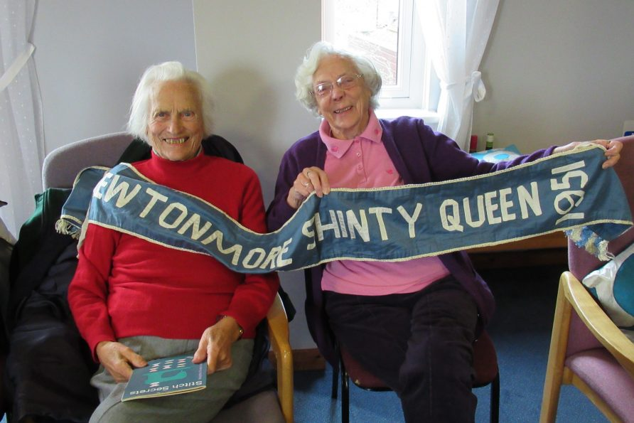 Two women pose with a banner saying Newtonmore Shinty Queen 1951   Community Archives and Heritage Group (CAHG)