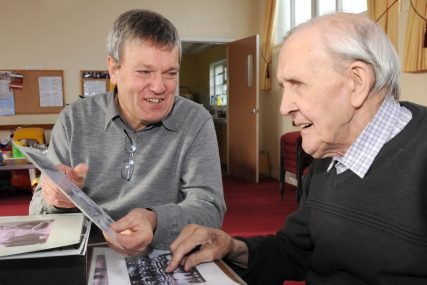 two men looking at old photgraphs of footballers | Courtesy of Michael White