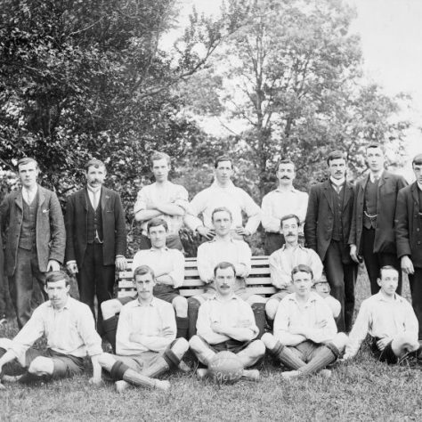 Black and white team photo with eleven footballers in white kit flanked by six men in suits | Fermanagh County Museum