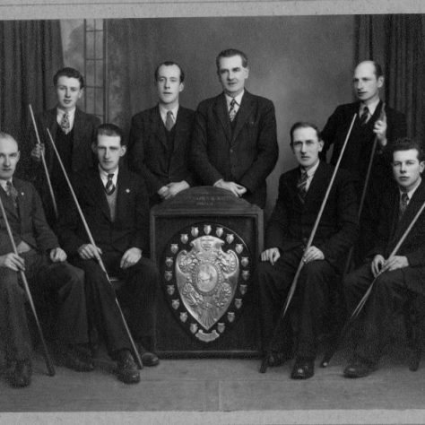 Black and white photo of eight men around a trophy with six of the men holding billiards cues | Fermanagh County Museum