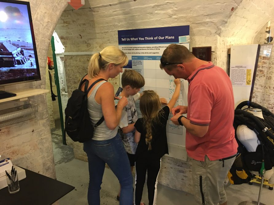 Images of young family working together to place their response on an evaluation survey on the wall of the Diving Museum | The Diving Museum