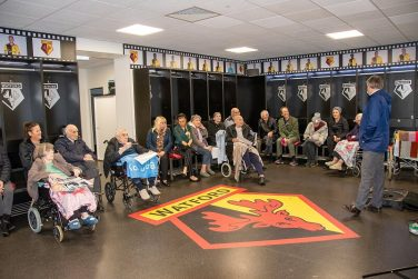 Group of visitors sitting around the Watford FC dressing room as part of a Stadium Tour