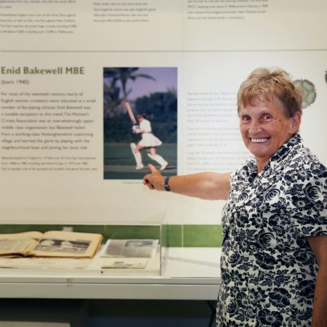 Woman points at photo of herself playing cricket   MCC Museum