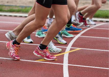 Shot of runners legs on an athletics track | Canva
