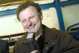 Mike Ingham smiling, holding mic while commentating